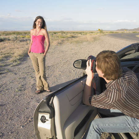 full length mirror: Young man taking a photograph of a young woman LANG_EVOIMAGES