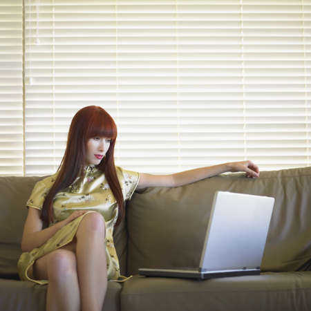 Young woman sitting on a couch and looking at a laptop Stock Photo - 16047036