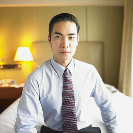 Portrait of a young businessman sitting on a bed Stock Photo - 16047075