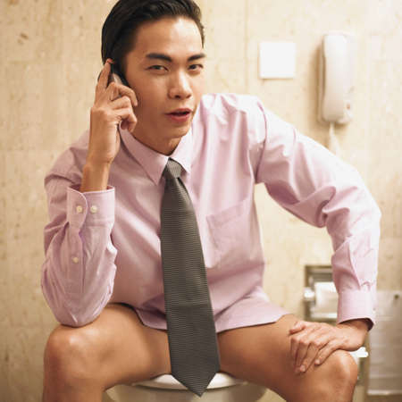 Young businessman sitting on a toilet talking on a mobile phone