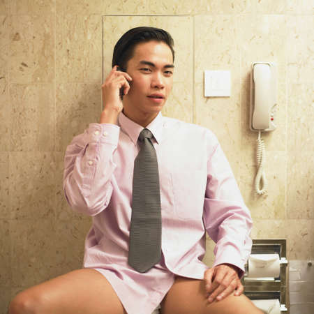 semi dress: Young businessman sitting on a toilet talking on a mobile phone