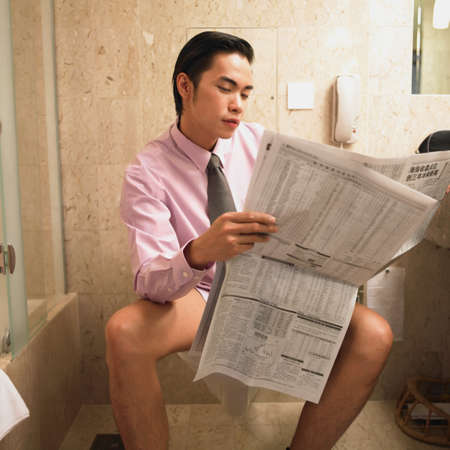 toilet: Young businessman sitting on a toilet reading a newspaper LANG_EVOIMAGES