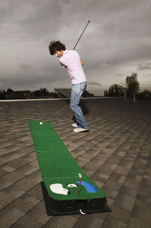 Side profile of a young man playing golf on an artificial turf Stock Photo - 16047123