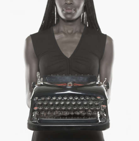 Mid adult woman holding a typewriter Stock Photo - 16047145
