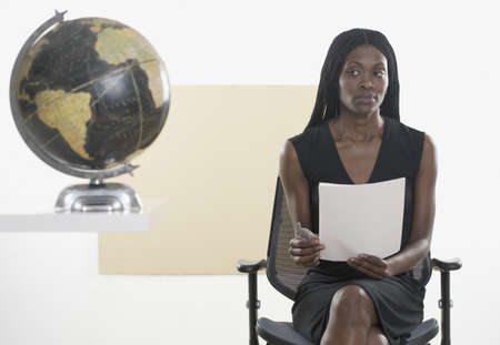 Mid adult woman sitting on a chair holding a document near a globe Stock Photo - 16047148