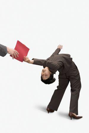 bending over: Businesswoman bending over backward and handing a file