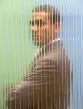 Side profile of a businessman standing behind the glass with his arms crossed Stock Photo - 16047161