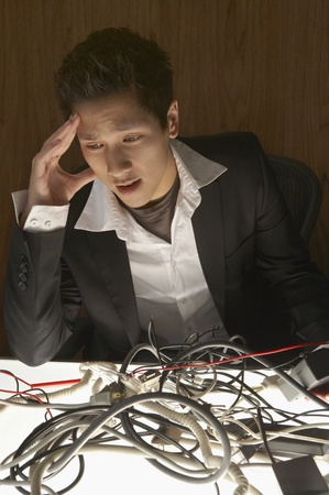 Businessman looking at cables with his head in his hand Stock Photo - 16047169