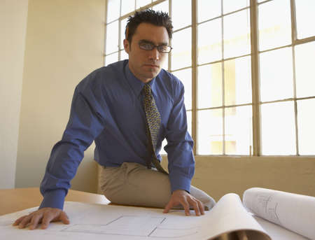 Portrait of a businessman sitting on a table with blueprints Stock Photo - 16047178