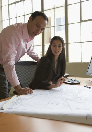 Businessman and a businesswoman looking at a blueprint Stock Photo