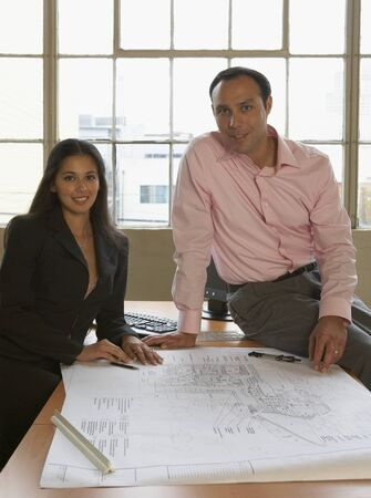 Portrait of a businessman and a businesswoman with blueprints on a table Stock Photo - 16047182