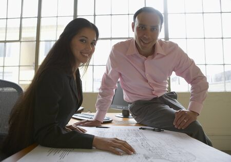 Portrait of a businessman and a businesswoman with blueprints on a table Stock Photo - 16047183
