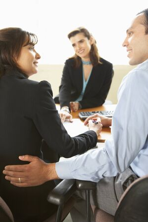 Businessman and two businesswomen discussing in an office Stock Photo - 16043261