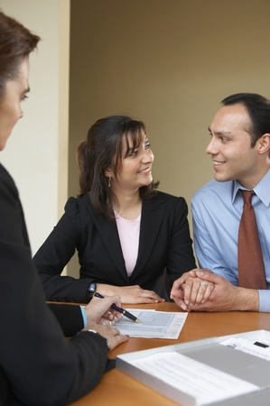 Businessman and two businesswomen sitting in an office Stock Photo - 16043260