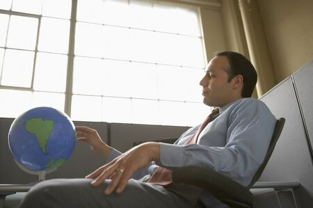 world at your fingertips: Low angle view of a businessman looking at a globe in an office LANG_EVOIMAGES