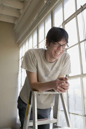 step ladder: Young man smiling and leaning on a step ladder