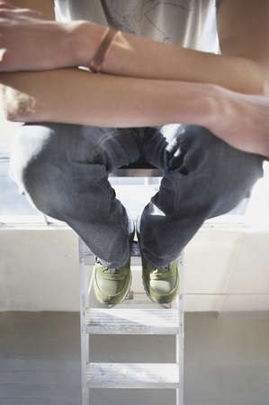 step ladder: Close-up of a young man sitting on a step ladder with his arms folded