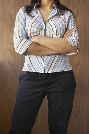 Mid section view of a mid adult woman standing with her arms folded