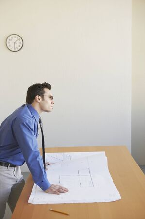 Side profile of a businessman leaning on a table Stock Photo - 16047204
