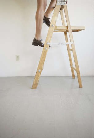 low section view: Low section view of a young woman climbing on a step ladder