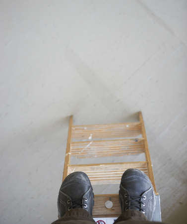 step ladder: High angle view of a mid adult mans feet on a step ladder LANG_EVOIMAGES