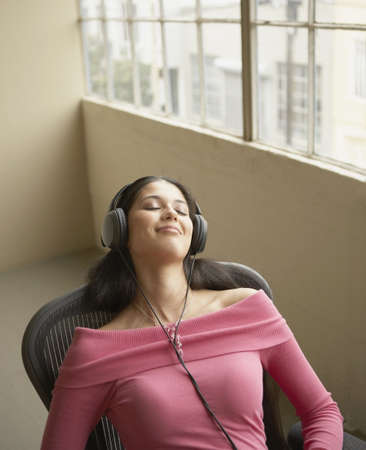 High angle view of a businesswoman wearing headphones and listening to music LANG_EVOIMAGES
