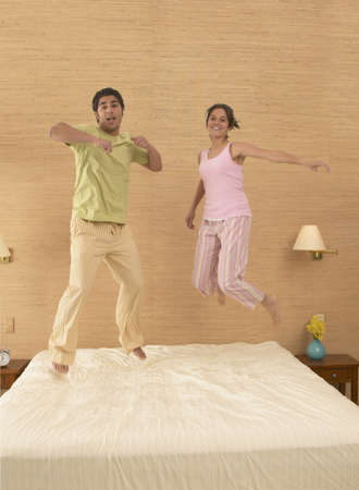 bed sheet: Portrait of a young couple jumping on a bed LANG_EVOIMAGES
