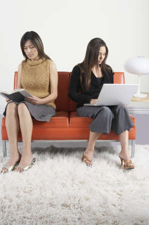 lamp shade: Two mid adult women sitting on a couch in the waiting room with a book and a laptop LANG_EVOIMAGES