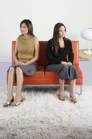 Two mid adult women sitting on a couch in the waiting room Stock Photo - 16047327