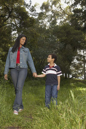 Mother and her son holding hands and walking in a garden Stock Photo - 16047335