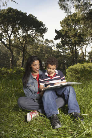 Mother and her son sitting in a garden and reading a book Stock Photo - 16047337