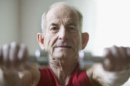 Portrait of a senior man exercising with dumbbells