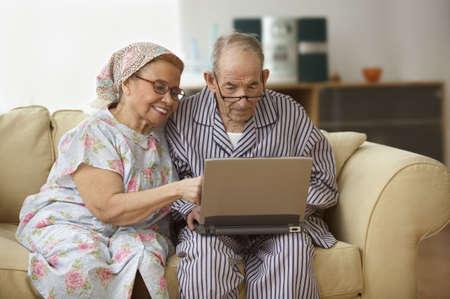 striped pajamas: Senior couple using a laptop