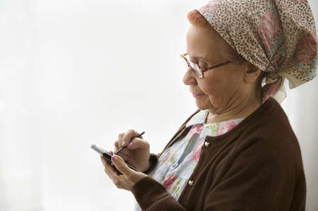 personal data assistant: Side profile of a senior woman using a personal data assistant