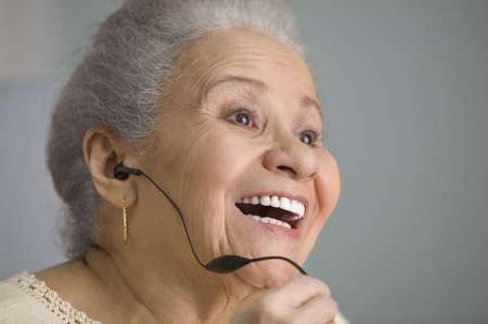 hands free: La mujer mayor con un dispositivo de manos libres