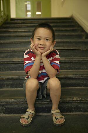 Portrait of a boy sitting on steps