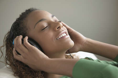 listening back: Young woman lying on her back listening to music