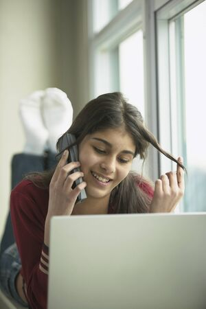 Close-up of a teenage girl talking on a mobile phone in front of a laptop Banco de Imagens