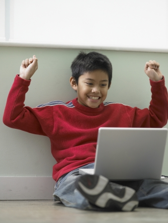 Boy sitting on the floor with a laptop on his lap