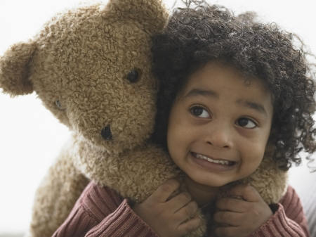 elementary age girl: Close-up of a boy carrying teddy bear on his back