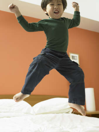 Low angle view of a girl jumping on a bed Stock Photo - 16047513