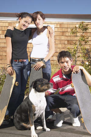 Portrait of two teenage girls and a teenage boy with their dog Stock Photo - 16047558