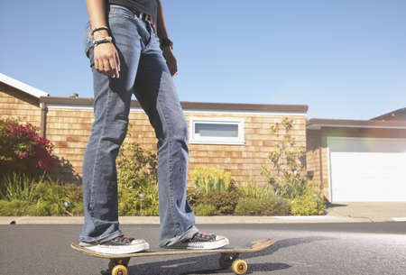low section view: Low section view of a teenage girl skateboarding on the street