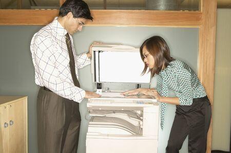 photocopier: Businessman and a businesswoman using a photocopier