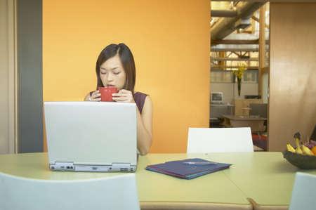 Businesswoman seduto davanti a un computer portatile bere caffè Archivio Fotografico