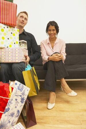 Young man sitting beside a young woman holding a stack of gifts Stock Photo - 16047689