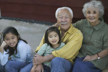Portrait of a senior couple sitting with their granddaughters LANG_EVOIMAGES