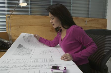 Side profile of a businesswoman looking at blueprints in an office Stock Photo - 16047710