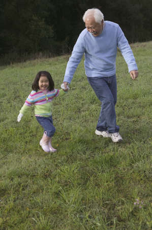 Grandfather holding hands of his granddaughter and walking in a field