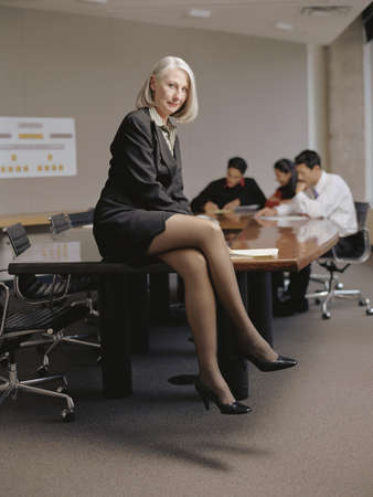 table skirt: Portrait of a businesswoman sitting on a conference table